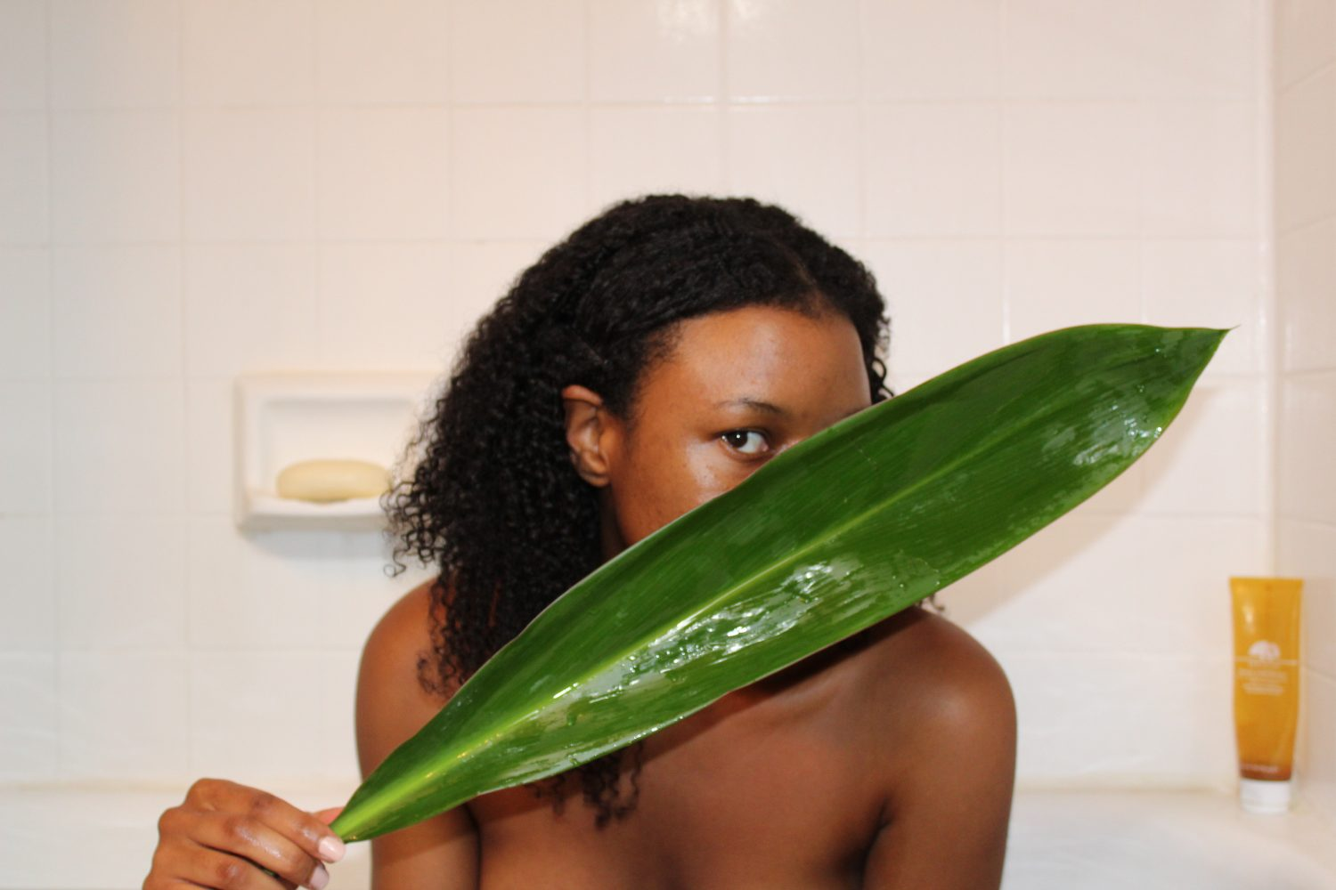 black girl holding leaf in front of face