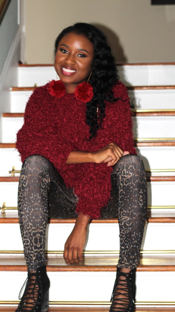 black woman in fuzzy red sweater sitting on stairs
