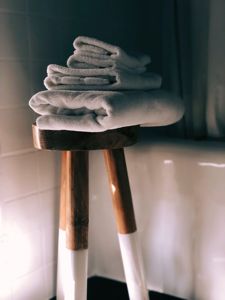 bath towels folded and stacked on a stool