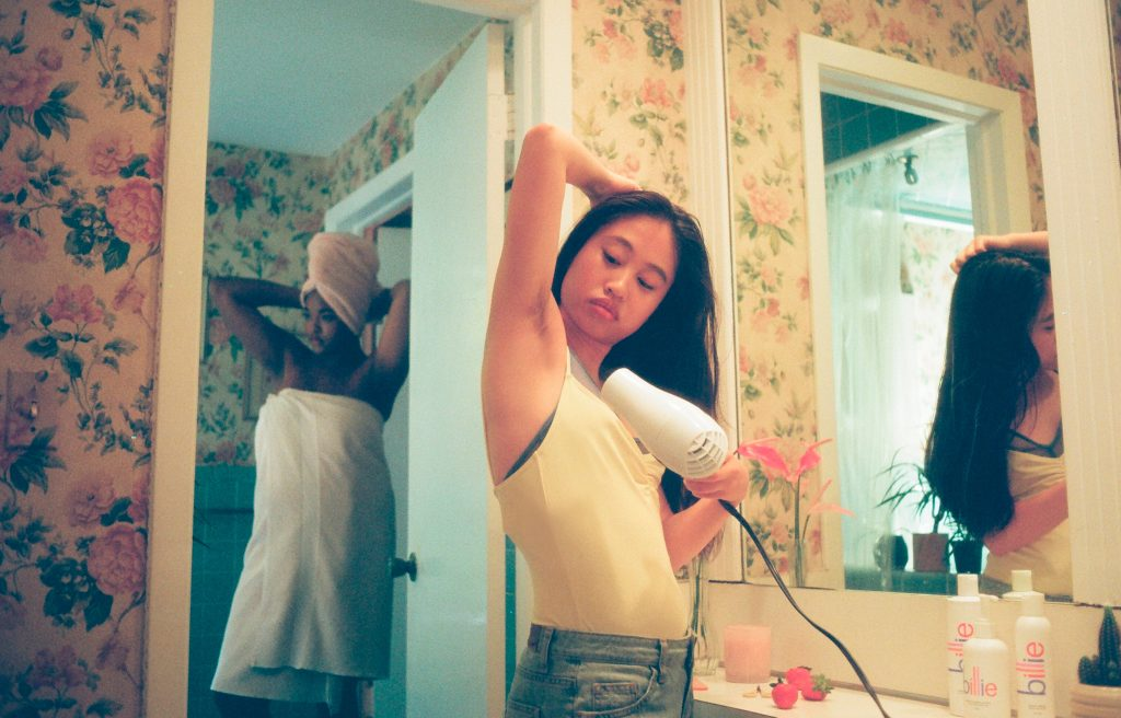girl blow drying armpits