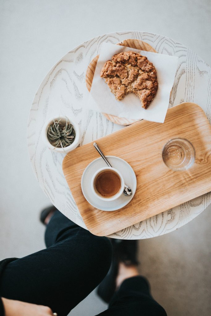 bamboo plate with coffee and half eaten cookie