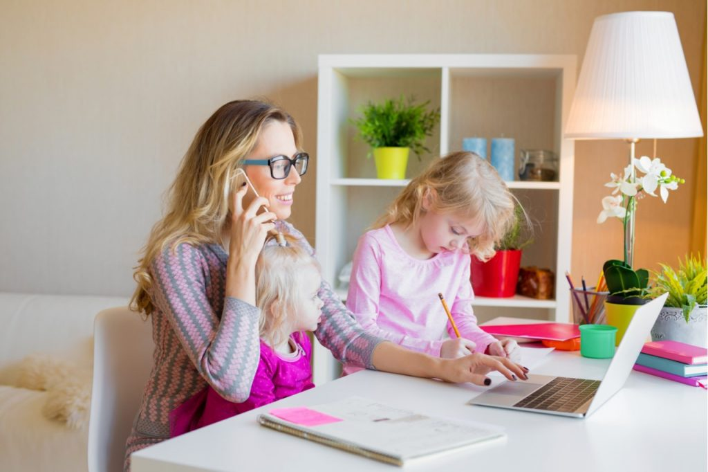 woman working from home with her daugther
