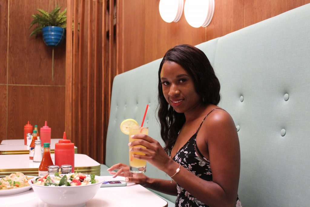 black woman holding a beverage in a restaruant