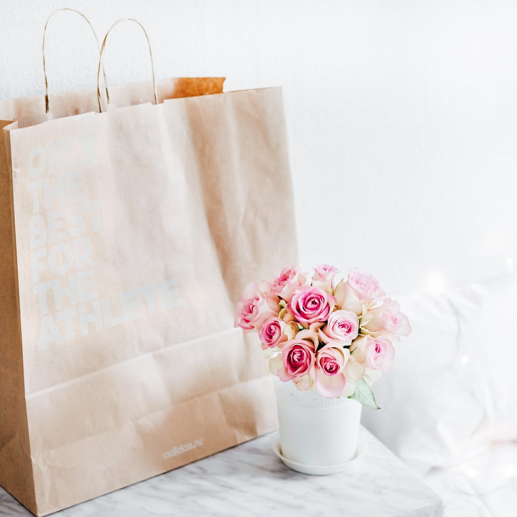 brown paper shopping bag and flowers